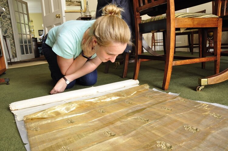 Dr. Megan Robb looking at textiles at the Palmer family archive in Devonshire